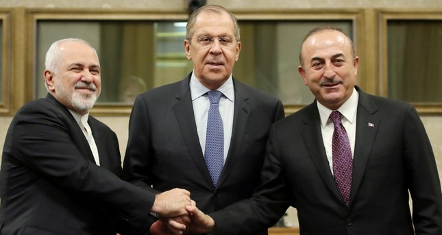 Russian Foreign Minister Lavrov, Turkish Foreign Minister Çavuşoğlu and Iranian Foreign Minister Zarif shake hands as they attend a news conference after talks on forming a constitutional committee in Syria, at the U.N. in Geneva. REUTERS Photo