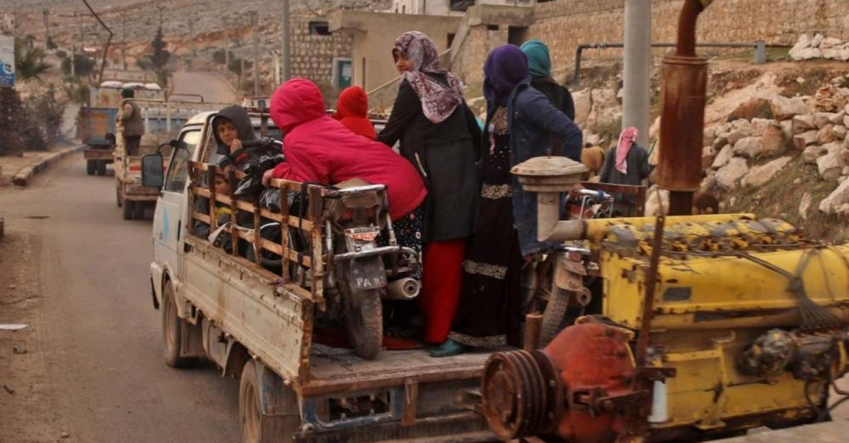 Vehicles carrying internally-displaced persons (IDPs) and their belongings drive through the town of Darret Ezza, about 30 kilometres northwest of the northern Syrian city of Aleppo, Feb. 17, 2020. (AFP Photo)