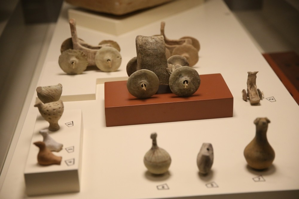 The toy chariot (above) and a rattle are among the artifacts discovered in child's grave.