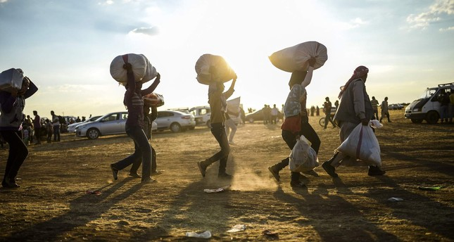 Syrian Kurds carry belongings as they cross the border between Syria and Turkey near the southeastern town of Suruç in Şanlıurfa province, on September 20, 2014.