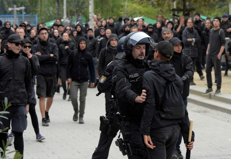 A police officer holds man as leftist demonstrators look on in Chemnitz, eastern Germany, Saturday, Sept. 1, 2018, after several nationalist groups called for marches protesting the killing of a German man last week. (AP Photo)