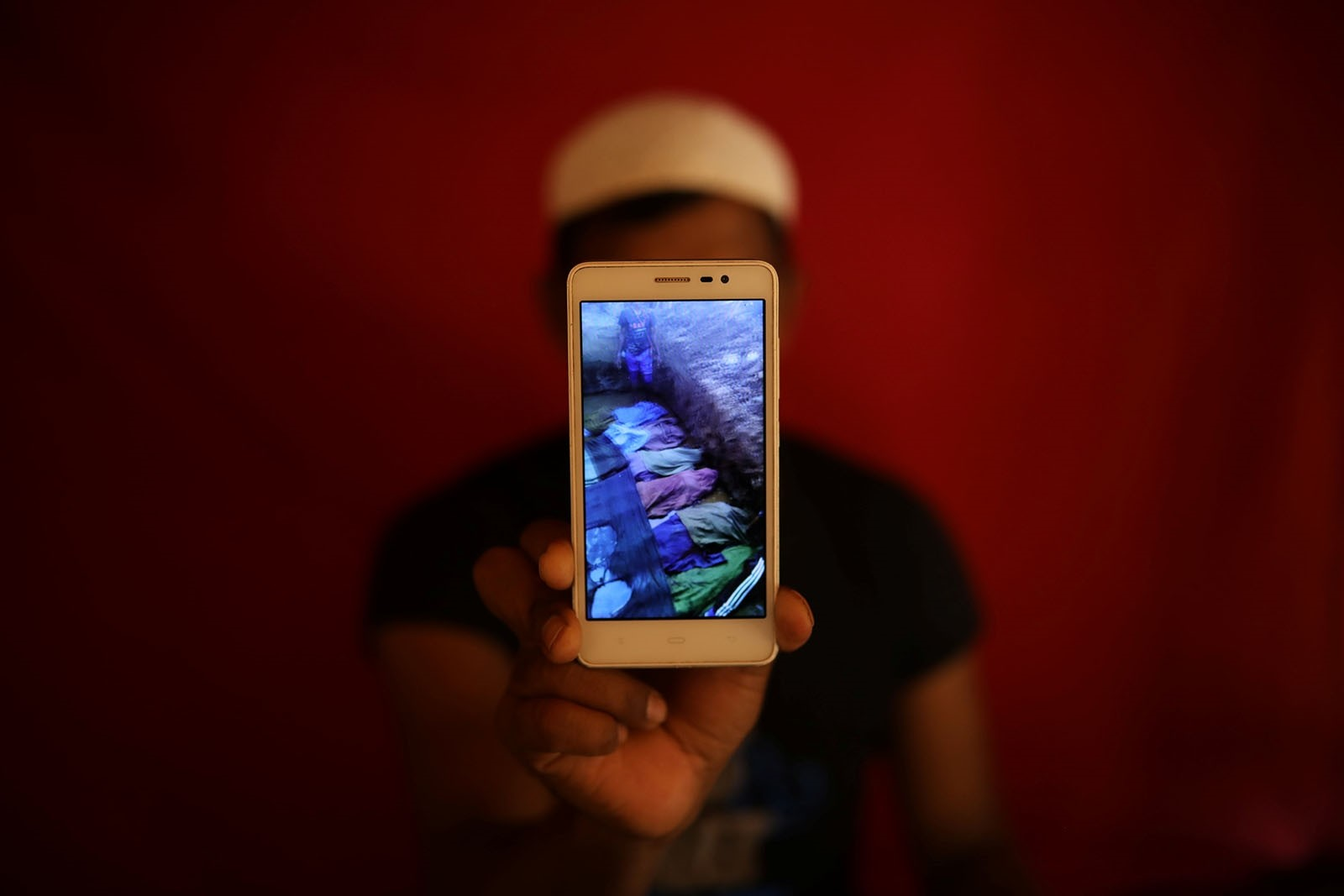 Islamic teacher Mohammed Younus holds a mobile phone on May 20, 2018 showing a video of what he says are the bodies of Rohingya Muslims killed by government forces in Kyauk Pan Du, Myanmar, on August 28, 2017.