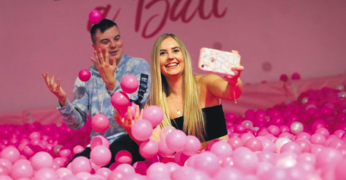 Young people pose in a bath of pink balls at The Selfie Factory.