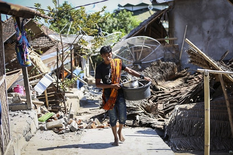 An Indonesian man collects his belongings from his collapsed house after an earthquake struck in North Lombok, West Nusa Tenggara, Indonesia, Aug. 6, 2018. (EPA Photo)