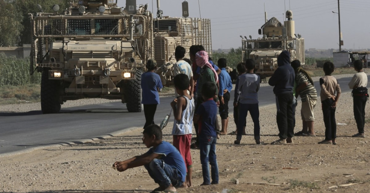 Syrians watch a U.S. armored convoy pass on a road to Raqqa, in northeastern Syria, July 26, 2017.