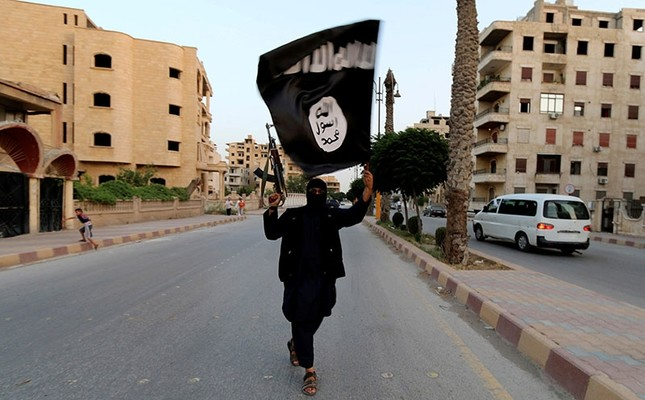 A member loyal to the Daesh waves the terrorist group's so-called flag in Raqqa, June 29, 2014. (Reuters Photo)