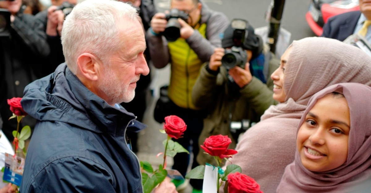 Opposition Labour Party leader Jeremy Corbyn holds a rose as he arrives at Finsbury Park mosque to mark national 'Visit my Mosque Day' in London on March 3, 2019. (AFP Photo)
