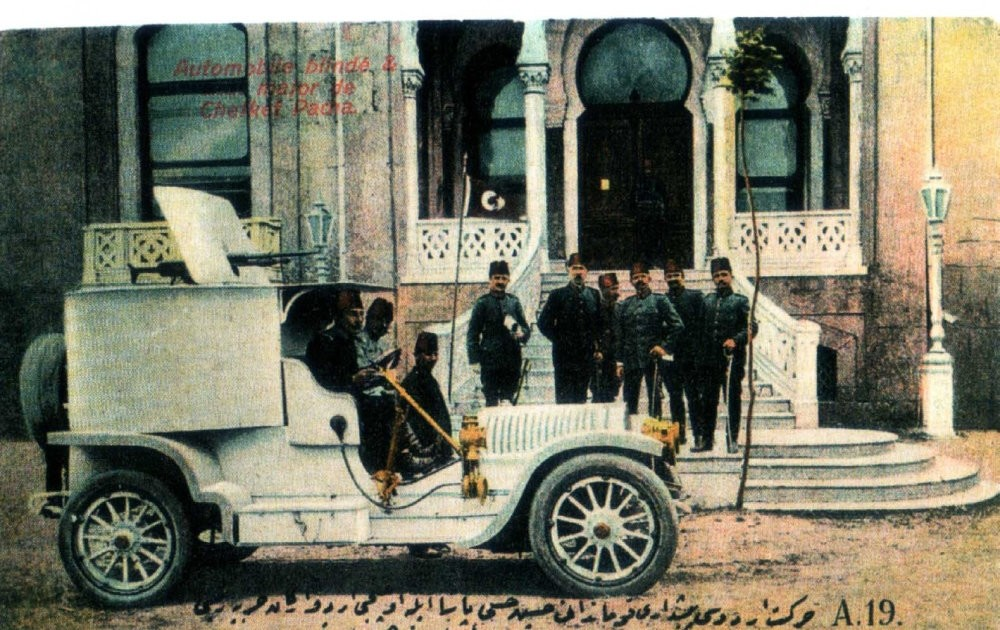 Hu00fcsnu00fc Pasha, Ali Ru0131za Pasha, Enver Pasha and other officers pose beside an armored vehicle in the early 20th century.
