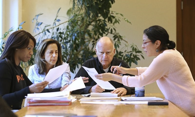 California Gov. Jerry Brown reviews a measure with his wife, Anne Gust Brown, second from left and staff Camille Wagner, left, Graciela Castillo-Krings, right, at his Capitol office, Sunday, Sept. 30, 2018, in Sacramento, Calif. (AP Photo)