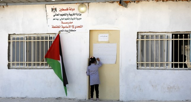 A Palestinian child knocks on the door of a school in the West Bank village of Jeb Deeb, near Bethlehem, Nov. 18.
