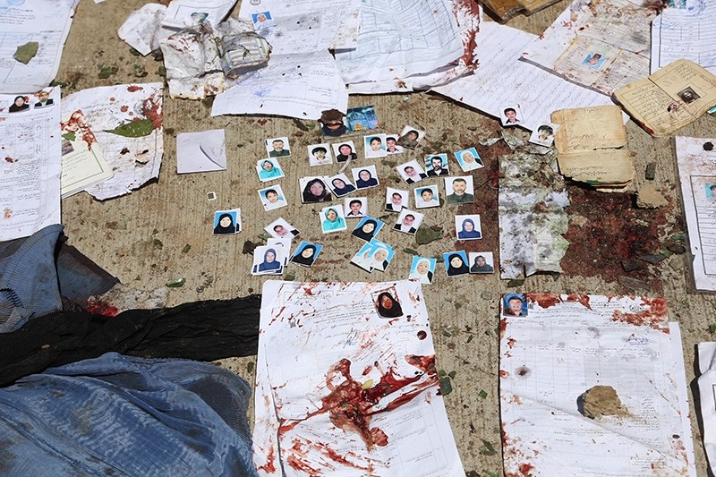 Blood-stained National ID papers and voters' photos are seen on the ground outside a voter registration center, after a suicide attack in Kabul, Sunday, April 22, 2018. (AP Photo)