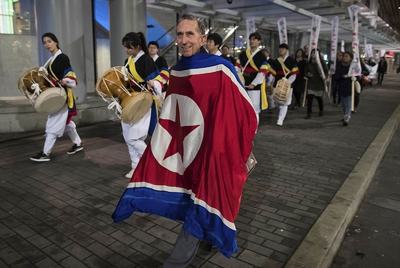 Draped in a North Korean flag, Peter Wilson, of New Zealand, marches with protesters outside the site of a summit on North Korea being hosted by Canada and the U.S., in Vancouver, British Columbia (AP Photo)