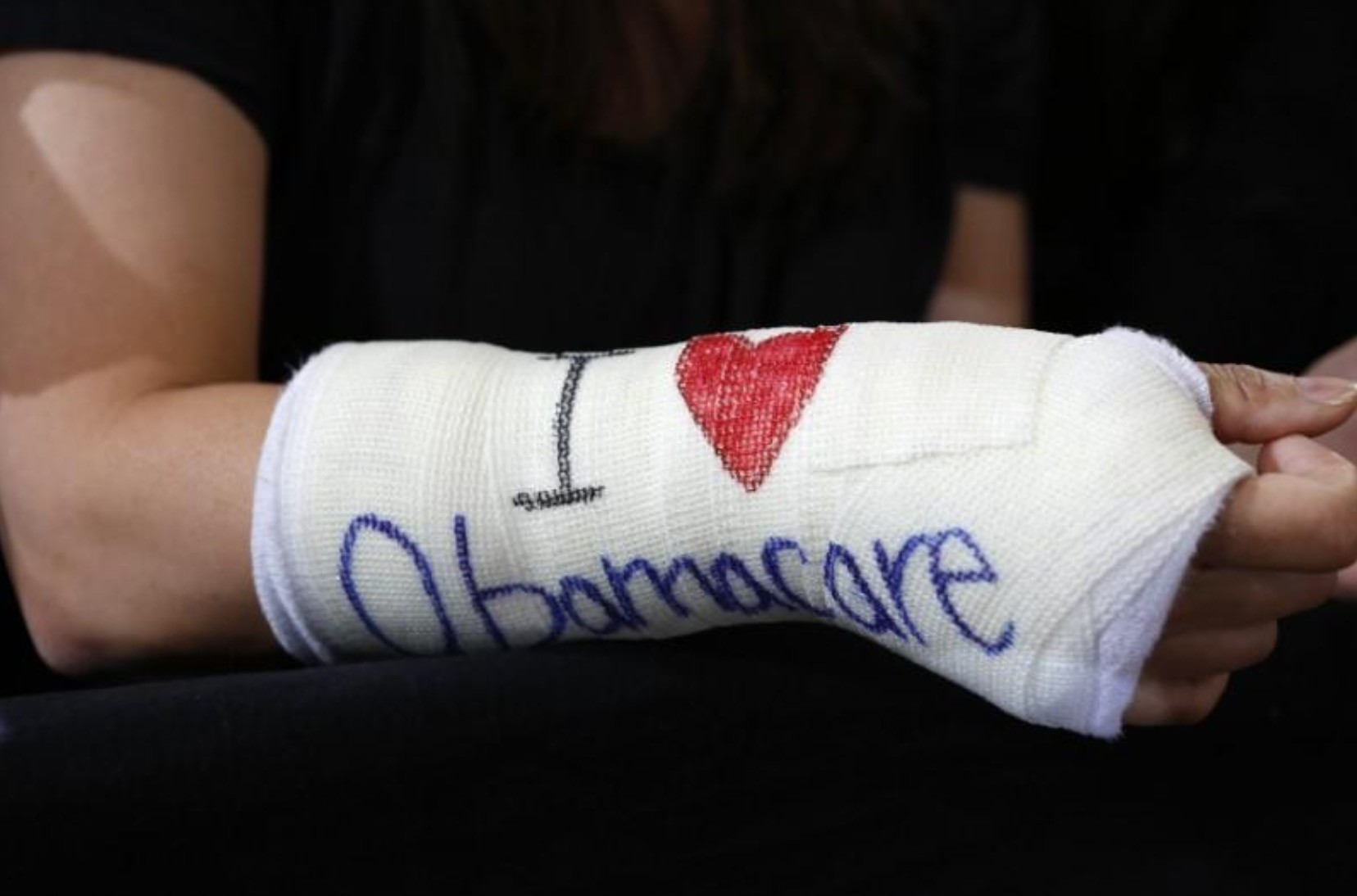 Cathey Park of Cambridge, Massachusetts wears a cast for her broken wrist with ,I Love Obamacare, written upon it prior to Obama's arrival to speak about health insurance at Faneuil Hall in Boston October 30, 2013. (Reuters Photo)