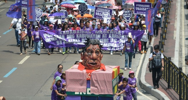 Activists from Gabriela push a carriage with an effigy of Philippines' President Rodrigo Duterte as they march toward Malacanang palace to commemorate International Women's Day in Manila on March 8, 2019. (AFP Photo)