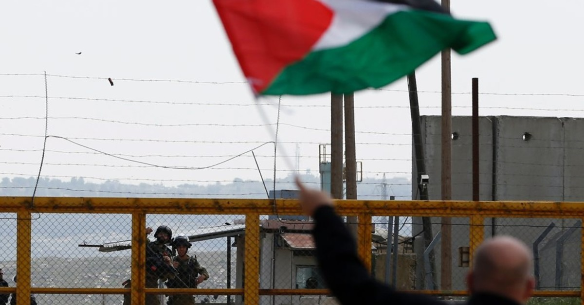 A Palestinian protester waves his national flag in front of Israeli security forces outside the compound of the Israeli-run Ofer prison near Betunia in the Israeli occupied West Bank, March 30, 2016.