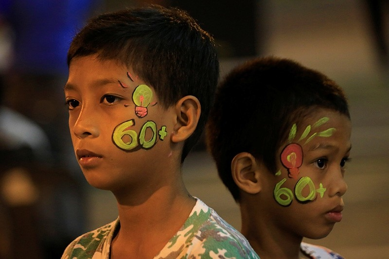 Boys with a painted number 60 on their faces, representing the 60 minutes of Earth Hour, are seen during Earth Hour outside a mall in Bacoor, Cavite city, south of Manila, Philippines March 24, 2018 (Reuters Photo)