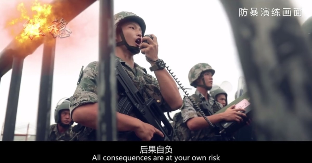 This screengrab taken from undated handout three-minute promotional video received on August 1, 2019 from China's People's Liberation Army (PLA) Hong Kong Garrison shows PLA soldiers warning ,protesters, during an ,anti-riot, drill in Hong Kong.(AFP)