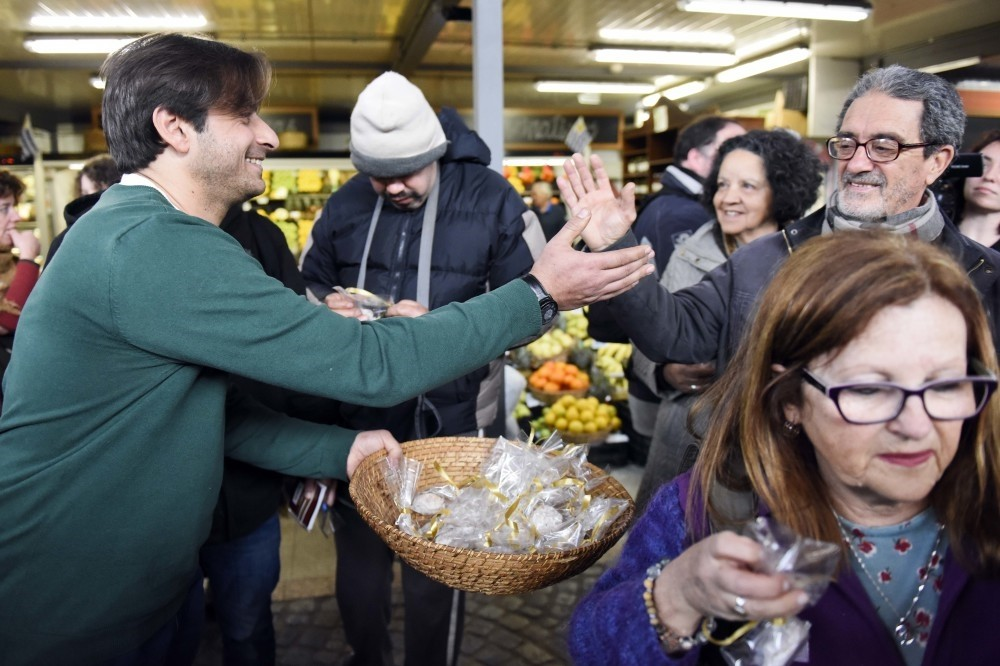 Syrian Ahmed Ahjam hands out samples of his work at the opening of his Middle Eastern pastry shop at the Mercado Agricola in Montevideo, Uruguay, Aug. 13.