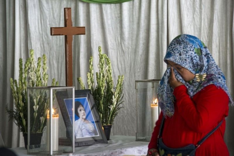 A mourner grieves by the memorial and coffin bearing the remains of Sri Puji, one of the victims killed during the May 13 Pantekosta church attack, ahead of her funeral in Surabaya, Indonesia, May 14.