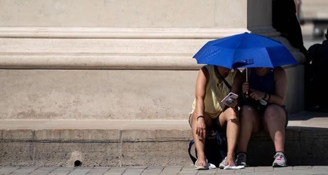 People use an umbrella to shelter from the sun near the Louvre Pyramid (Pyramide du Louvre) during a heatwave in Paris on June 26, 2019. (AFP Photo)