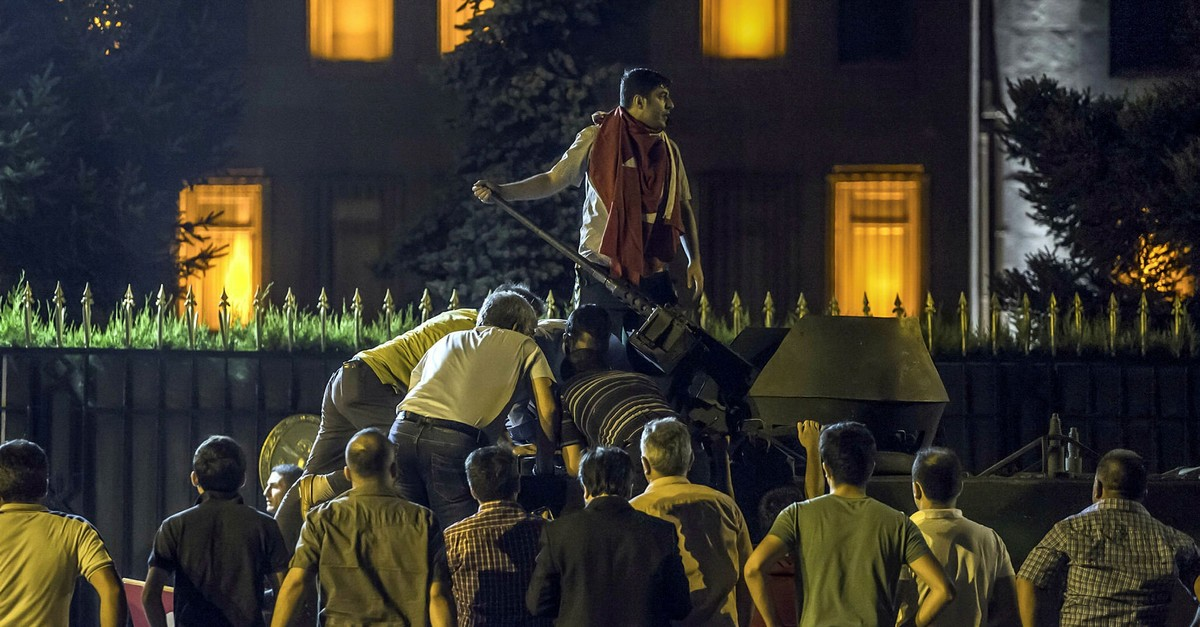 An anti-coup crowd climbs on a tank captured from FETu00d6 putschists outside the military headquarters in the capital Ankara during the night of the July 15 coup attempt, 2016.