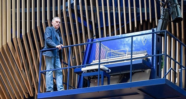 David Klavins stands next to his new creation, the M470i vertical concert grand piano, with a height of 4,70 meters, at the new Lativa concert hall in Ventspils, Latvia, on July 23, 2019.