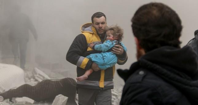 مسعف من الدفاع المدني ينتشل طفلة مصابة في القصف على الغوطة (الأناضول)