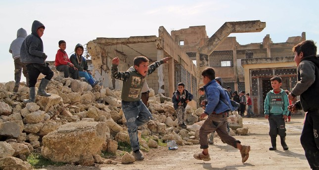 Children play in the yard of a school that was partially destroyed during battles in the village of Kufayr, in Syria's Idlib Governorate, Feb. 4, 2019.