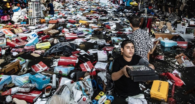 Shopkeepers try to salvage goods floating in floodwaters at an underpass in Eminönü, Aug. 17, 2019.