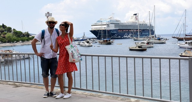 German tourists pose in front of a cruise ship named Mein Schiff 2 in Bodrum, western Muğla province. (AA Photo)