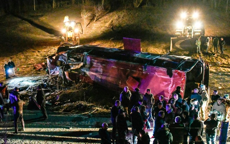 Bystanders and rescue personnel gather near the wreckage of a bus on a road near Skopje on February 13, 2019. (AFP Photo)