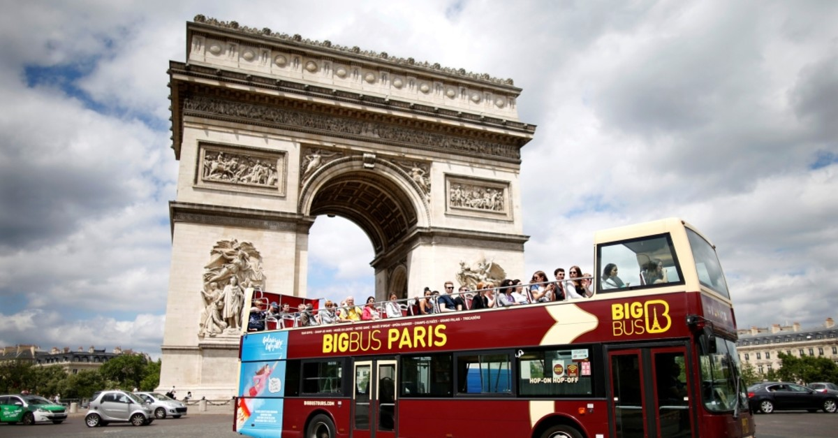 Tourists ride in an open-air double-decker bus past the Arc de Triomphe in Paris.