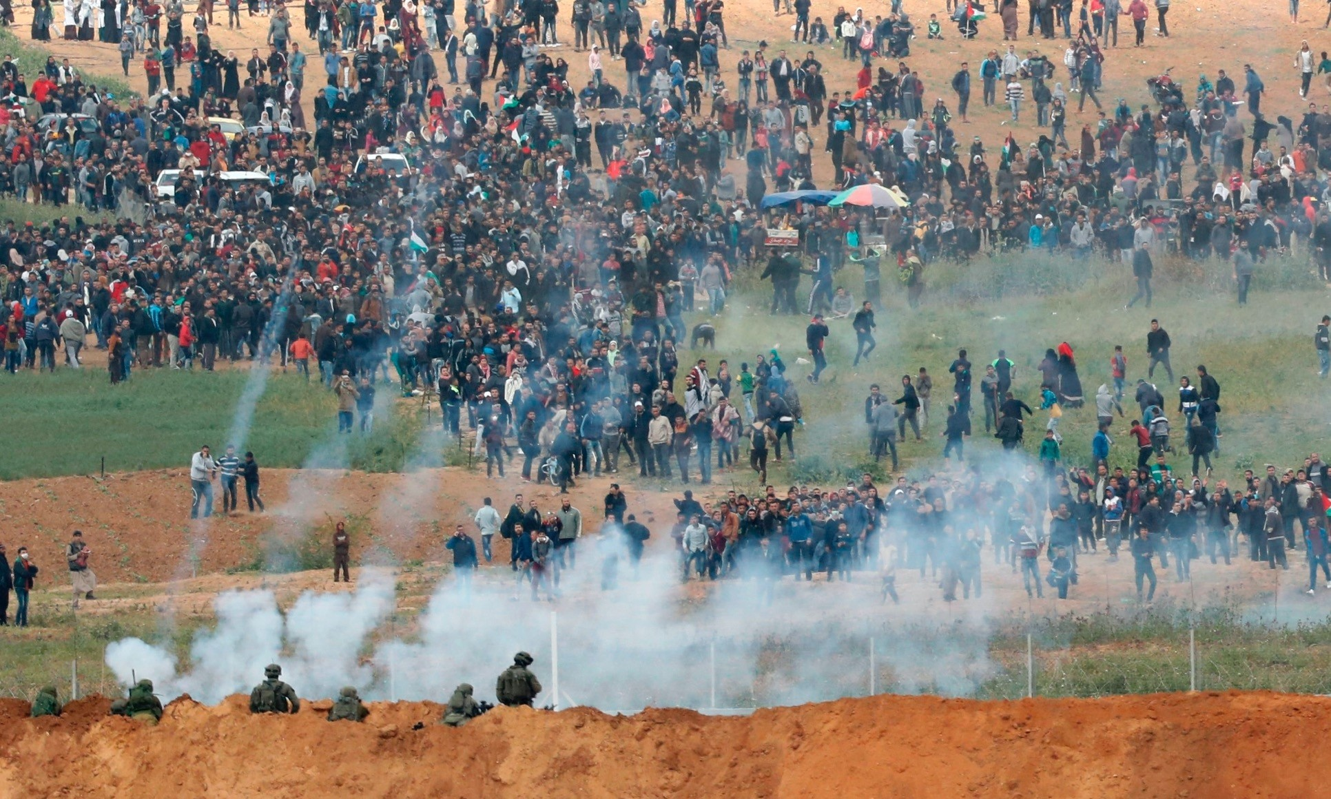 This picture from the southern Israeli kibbutz of Nahal Oz across the border from the Gaza strip shows tear gas grenades being thrown during a Palestinian tent city protest commemorating Land Day, with Israeli soldiers seen below in the foreground.