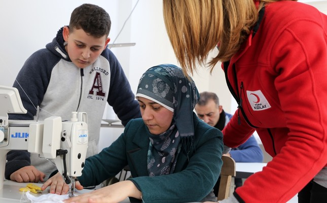 A Red Crescent worker shows a Syrian woman how to sew at a workshop in İzmir, Mar. 1, 2019.
