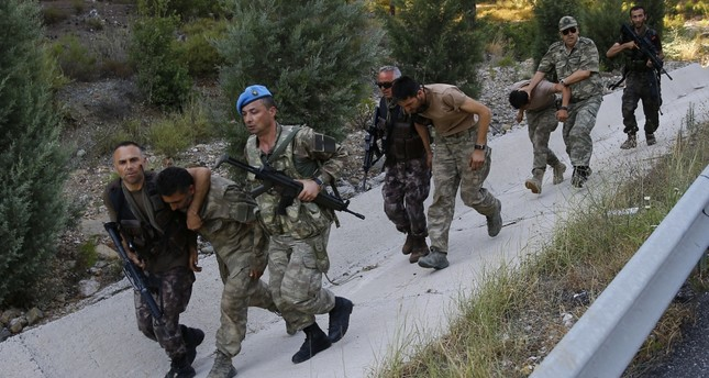 Soldiers and members of police's special forces unit accompany officers linked to the Gülenist junta after their capture near the southwestern town of Marmaris last month.