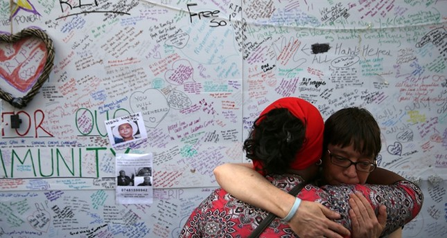 Two women embrace in front of a messages left on a wall of condolence following the blaze at Grenfell Tower, a residential tower block in west London on June 15, 2017. (AFP Photo)