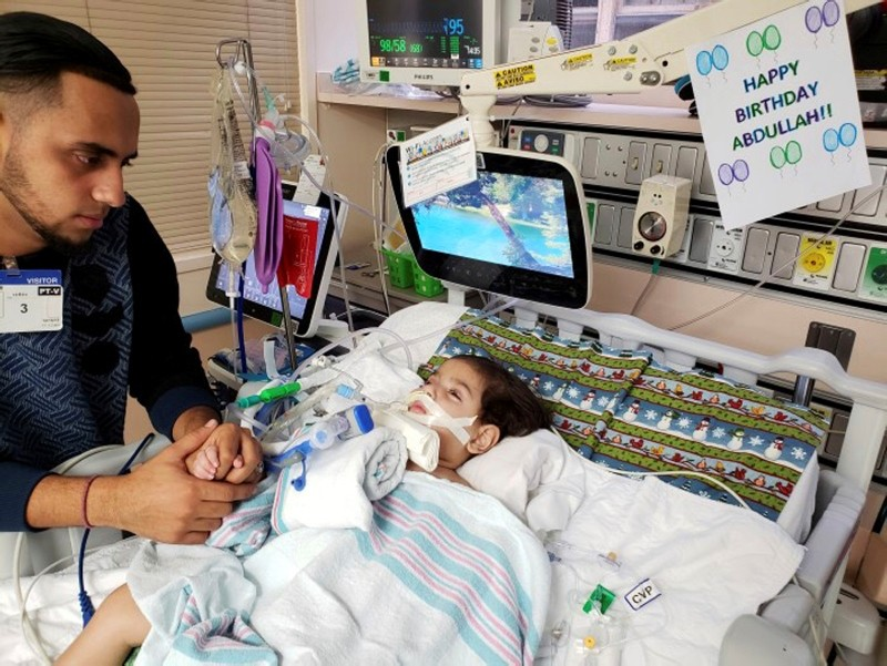 This recent but undated photo, released Monday, Dec 17, 2018 by the Council on American-Islamic Relations in Sacramento, shows Ali Hassan with his dying 2-year-old son Abdullah in a Sacramento hospital. (Council on American-Islamic Relations via AP)