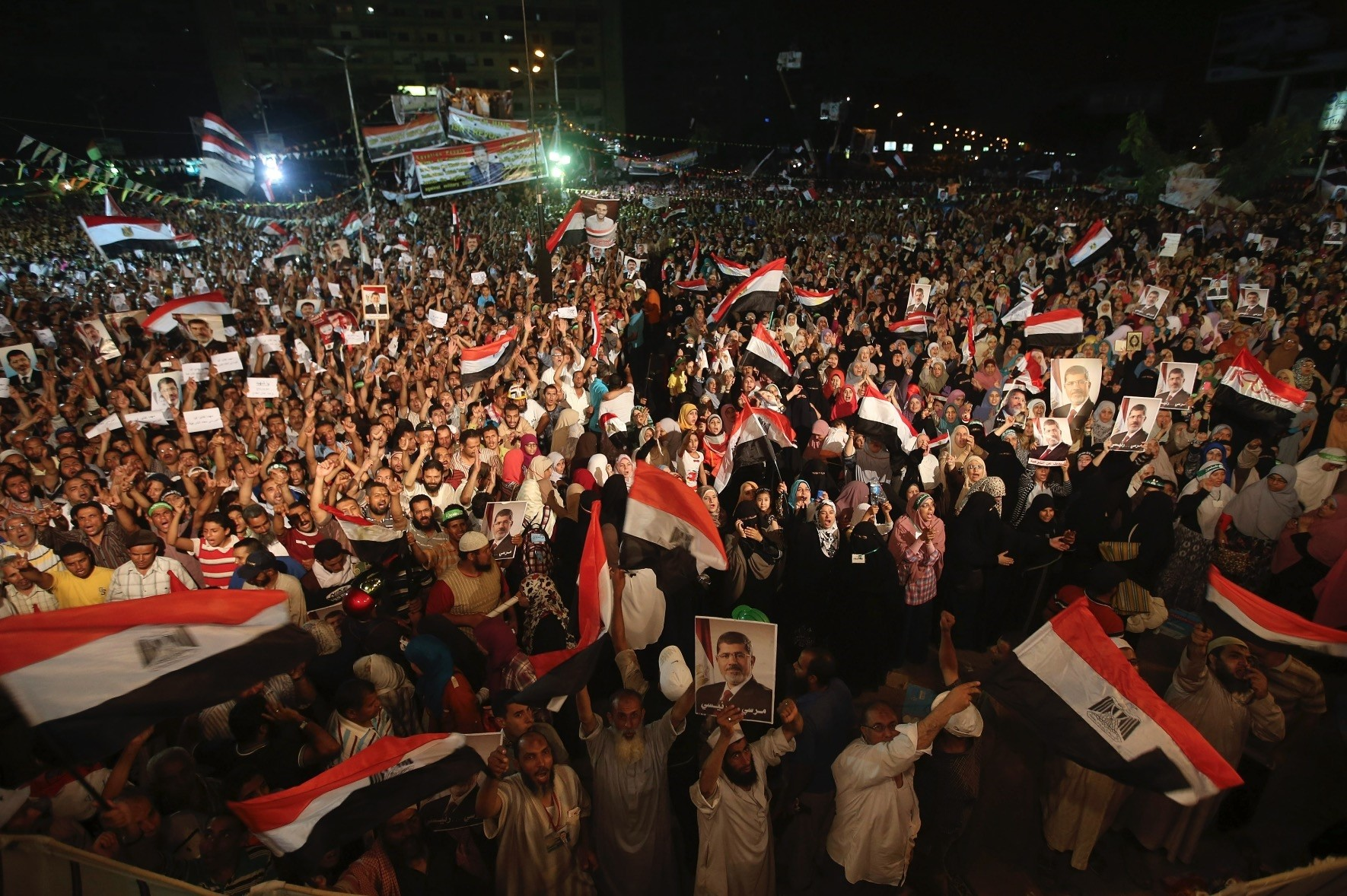 Supporters of Egyptu2019s first democratically elected President Mohammed Morsi hold his portraits and wave flags in Cairo, July 10, 2013 a month before Egyptian military tanks ran over protestors in Tahrir square.