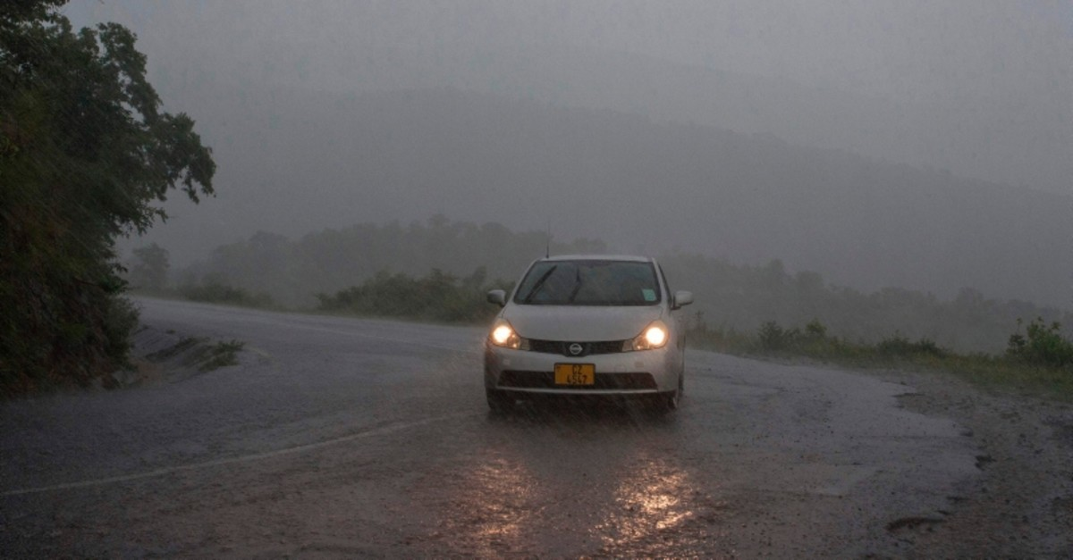 This picture taken on March 15, 2019 shows a vehicule as rain, which is believed to be the beginning of Tropical cyclone Idai coming from central Mozambique, falls in the flooded districts of Chikwawaa and Nsanje in southern Malawi (AFP Photo)