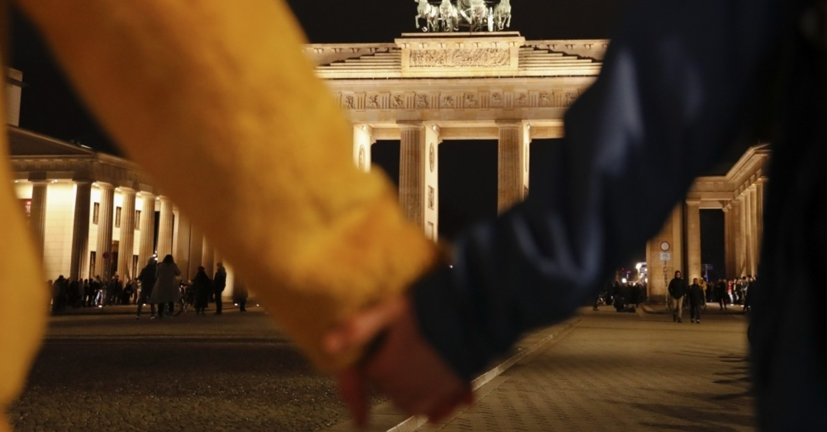 People hold hands as they form a human chain, during a vigil for victims of last night's shooting in the central German town Hanau, at the Brandenburg Gate in Berlin, Germany, Thursday, Feb. 20, 2020. (AP Photo)