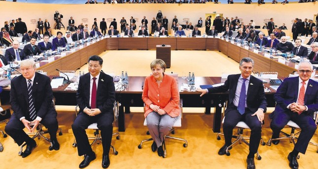 (From L - R) U.S. President Trump, Chinese President Xi, German Chancellor Merkel, Argentinia's President Macri and Australian PM Turnbull sit for photographers at the start of the first working session of G20 meeting, Hamburg, Germany, July 7, 2017.