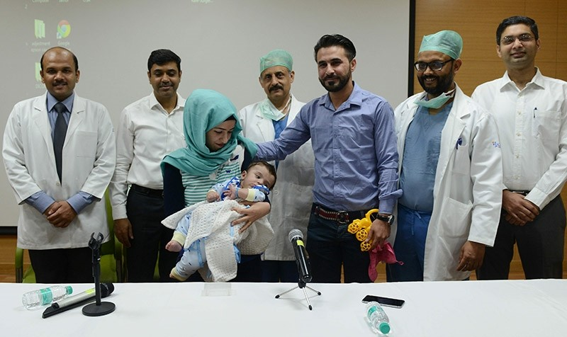 Iraqi parents Gufran Ali (3L) and Sarwed Ahmed Nadar (3R) pose with their eight month old son Karam (C) and physicians during a press conference at a hospital in Noida on April 14, 2017. (AFP Photo)