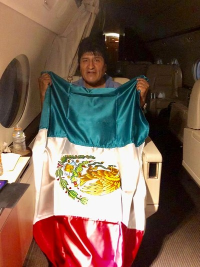 Morales holds a Mexican flag onboard a Mexican government's aircraft Nov. 11, 2019. (Mexican Foreign Minister Marcelo Ebrard via Twitter via Reuters)