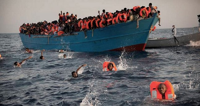 Migrants, mostly Eritrea, jump into the water from a crowded wooden boat as they are helped by members of an NGO during a rescue operation on the Mediterranean, about 21 kilometers north of Sabratha, Libya.