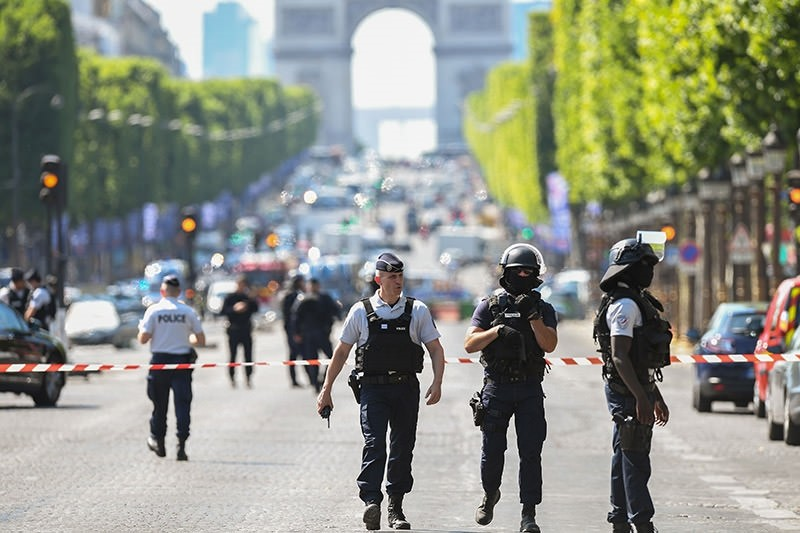 Police officers and anti-riot police officers patrol the Champs-Elysees avenue on June 19, 2017 on the Champs-Elysees avenue in Paris, after a car crashed into a police van before bursting into flames. (AFP Photo)