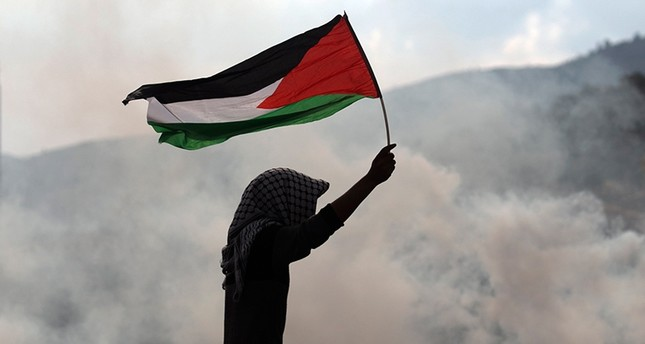 A protester waves a Palestinian flag amid tear gas fumes during clashes with Israeli security forces near the Huwara checkpoint, south of the Israeli-occupied West Bank city of Nablus, Dec. 15, 2017. (AFP Photo)