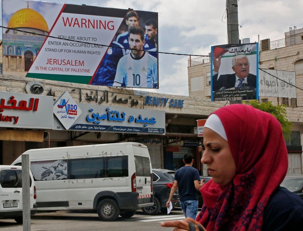 Poster erected on a main street in the West Bank town of Hebron denounces the planned friendly football match between Argentina and Israel and calls Argentina's star Lionel Messi (portrait) to boycott the match.