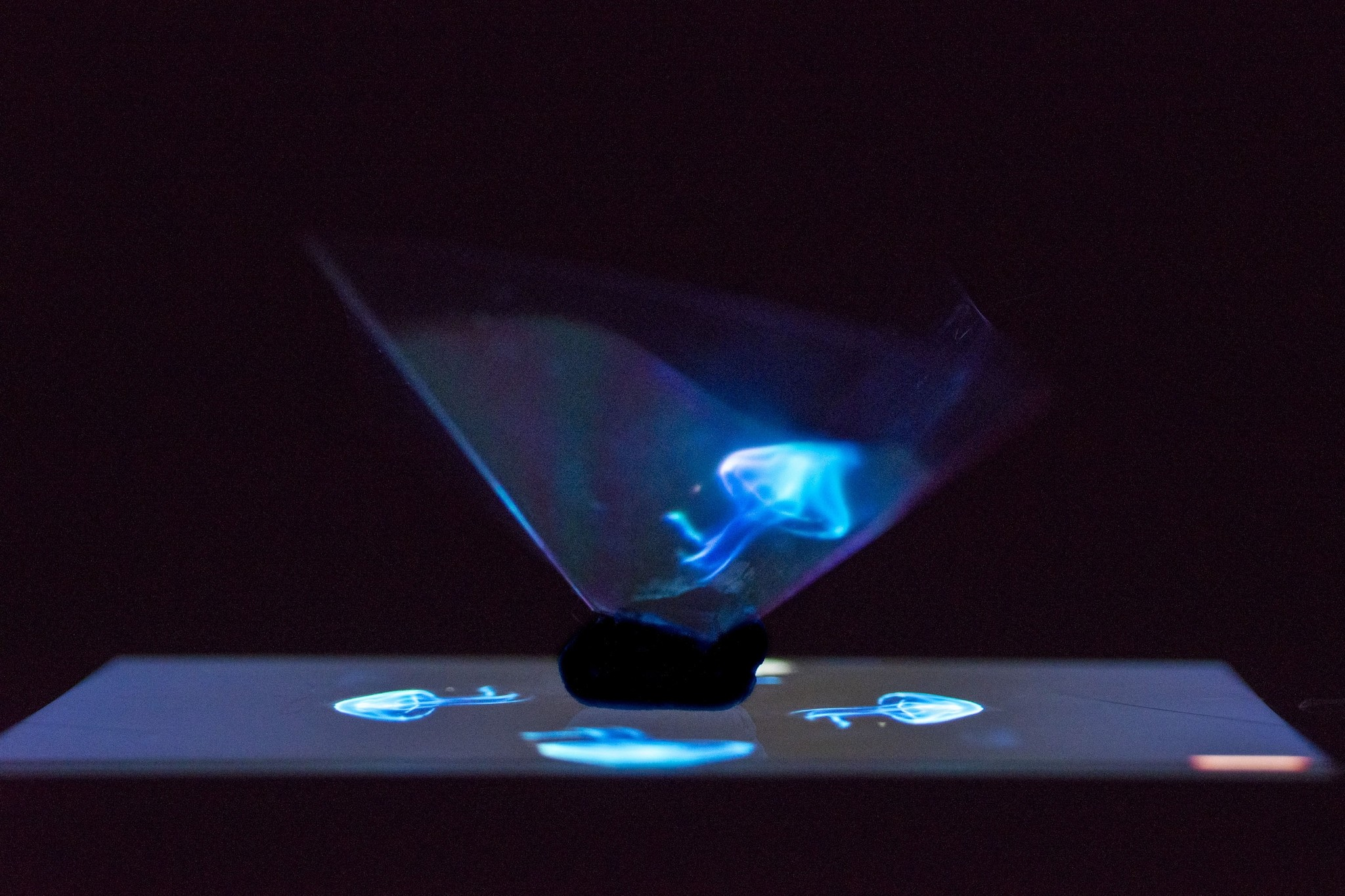 Using plastic pieces and scissors, the participants of the u201cMini Hologramu201d workshop design their own hologram pyramids, put them on their mobile screens and create 3D illusions via hologram videos.