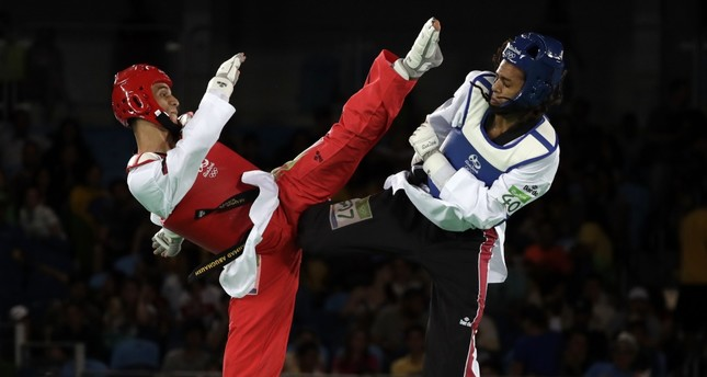 Ghofran Ahmed of Egypt (R) and Ahmad Abu Ghosh of Palestinian origin Jordanian compete in a men's Taekwondo 68-kg event at the 2016 Summer Olympics in Rio de Janeiro, Aug. 18, 2016.