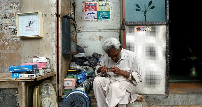 An elderly man checks a wristwatch while repairing it at his makeshift stall along a sidewalk in Karachi, Pakistan July 29, 2017 (Reuters Photo)